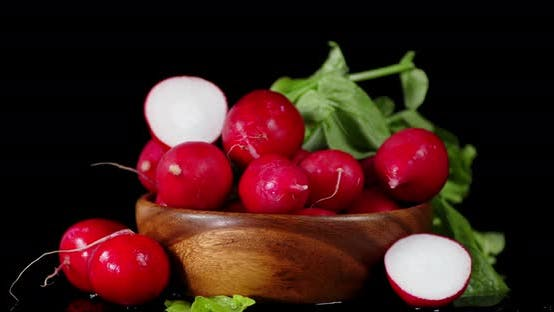 Fresh Radishes on a Wooden Plate Slowly Rotates.