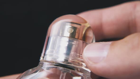 Thumbnail for Man Takes Off Cap From Perfume Bottle on Dark Background