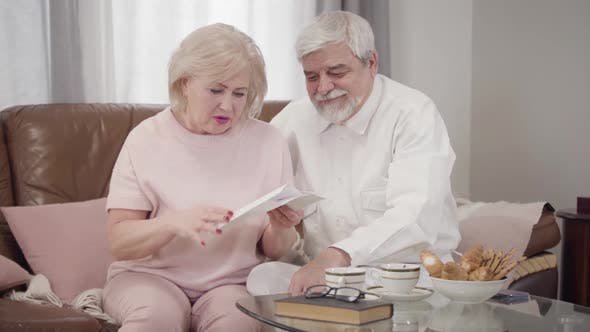 Thumbnail for Anxious Senior Caucasian Woman Opening Letter and Touching Face with Hand, Hansome Old Husband