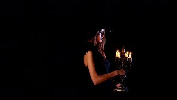 Thumbnail for Young Sexy Witch Blows Out the Candles on a Black Background
