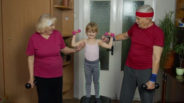 Thumbnail for Granddaughter and Mature Grandparents in Sportswear Making Sports Jogging Workout Exercises at Home