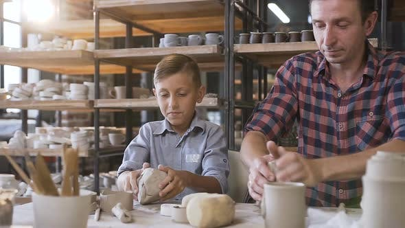 Thumbnail for Attractive Caucasian Man and Liitle Cute Boy Kneading Clay for Pots