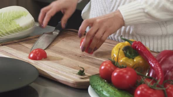 Thumbnail for Cropped Shot of a Woman Slicing Tomato on a Wooden Cutting Board