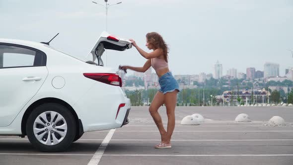 Beautiful Slim Woman in Short Denim Shorts Sexually Goes To Her Car and Opens Trunk To Put on Hat