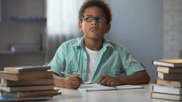 Thumbnail for Afro-American Boy Thinking on School Essay, Smart Kid Doing Homework, Education
