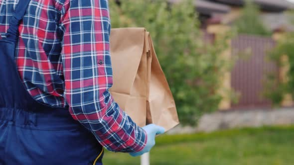 Thumbnail for Rear View: A Delivery Service Employee Carries Food Bags To the Customer's Home