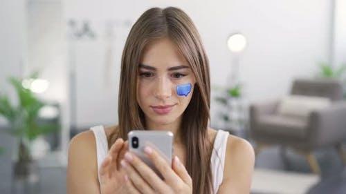Nahaufnahme Porträt von jungen Angenehme Frau mit ihrem Handy sitzen zu Hause
