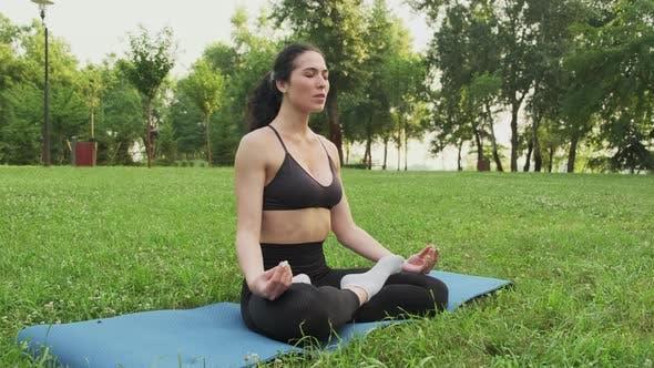 Beautiful Woman Meditating in City Park