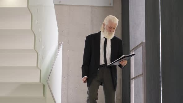 Senior Man in Suite with Notepad Going Downstairs in a Building