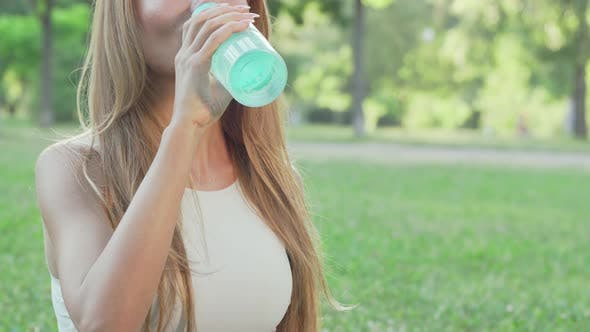 Thumbnail for Healthy Fit Woman Drinking Water While Doing Yoga in the Park