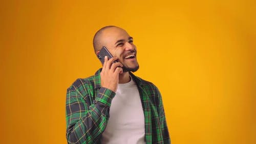 Young African American Man Talking on the Phone Against Yellow Background