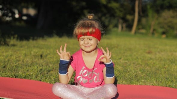 Thumbnail for Child Sitting on Mat and Performing Yoga Meditation Outdoors in Park. Girl Doing Yoga Exercises