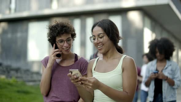 Thumbnail for Happy Women Looking at Smartphone and Laughing