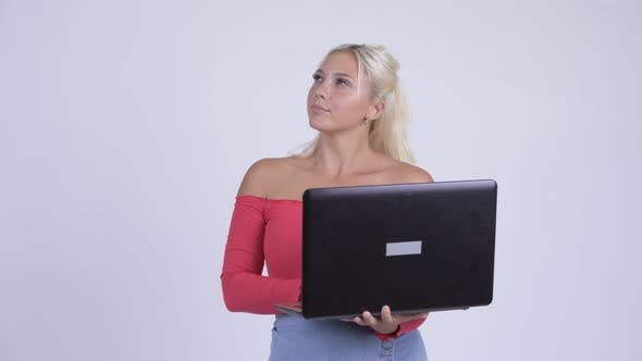 Thumbnail for Happy Young Beautiful Blonde Woman Thinking While Using Laptop