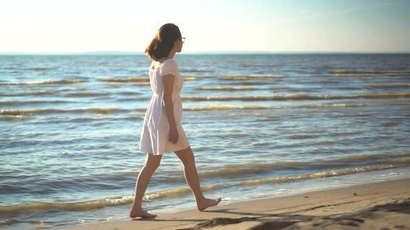 Thumbnail for Attractive Young Woman Walks Along the Sea Beach. A Girl in a White Dress Walks Barefoot Along the