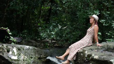 Woman sitting swing foot on the rock in the forest