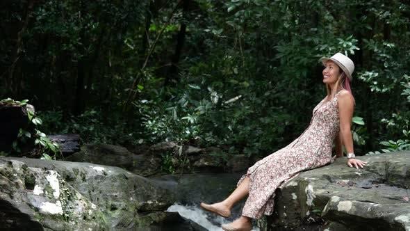 Femme assise pied balançoire sur la roche dans la forêt