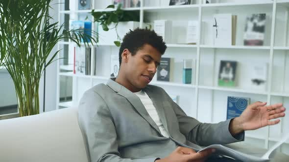 Black Businessman Reading Paper on Sofa