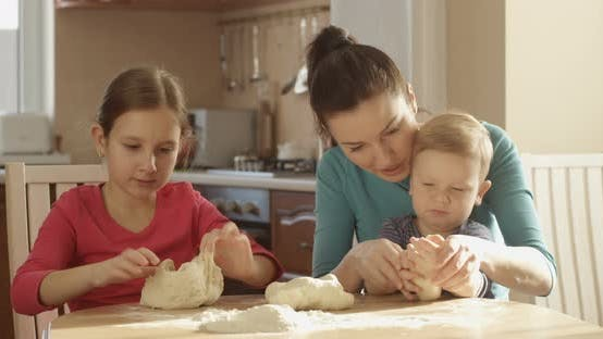 Thumbnail for Happy Family Cooking Together Kneading Dough In Kitchen With Mother Daughter And Son On Sunny Day