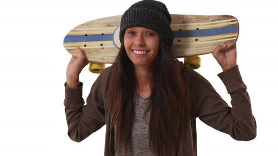 Thumbnail for Millennial girl with skateboard over her shoulders looking at camera