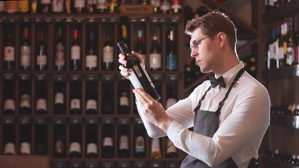 Thumbnail for Elegant Wine Seller Holding a Bottle of Wine and Reading Label in a Wine Store