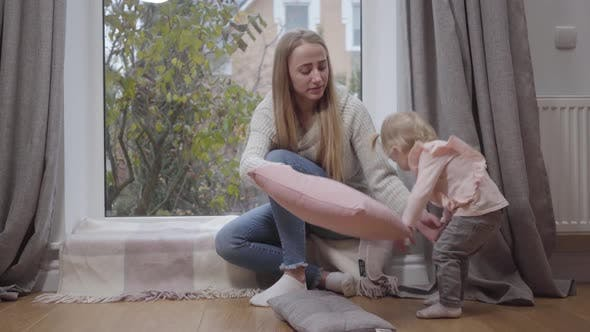 Thumbnail for Young Attractive Caucasian Woman Sitting at Low Windowsill and Talking To Little Girl
