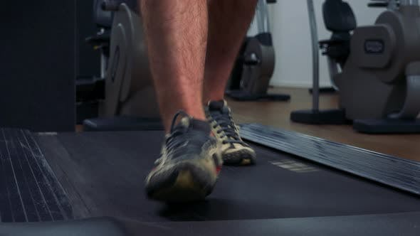 Thumbnail for A Fit Man Walks on a Treadmill in a Gym - Front Closeup on the Feet