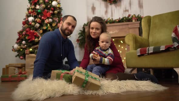 Cover Image for Happy Family Celebrating Christmas Together Mother, Father and Little Baby Sitting on the Floor