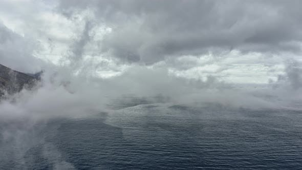 Backward Aerial Tracking Shot of Ocean Waters and Fog Covering the Frame