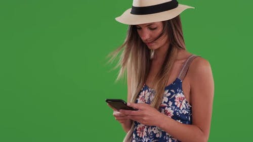 Woman in floral print romper and fedora texting on mobile phone on greenscreen