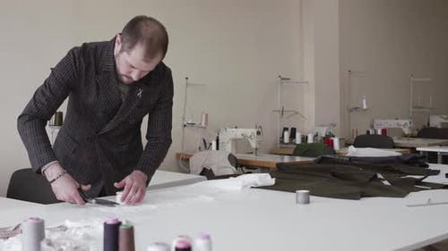 The Fashion Designer Cutting a Cloth Curve on a Desktop in Dress Atelier