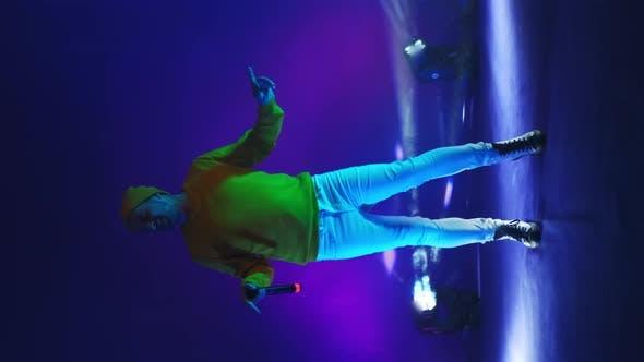 Vertikales Video. Brand Lustige Sängerin in gelber Kleidung Tanzen und Gesang mit einem Mikrofon in