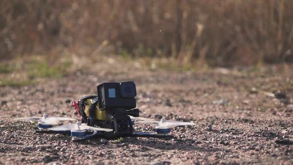 Thumbnail for FPV Racing Drone Takes Off From a Dirt Surface Raising Dust and Stones