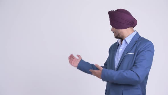 Thumbnail for Happy Bearded Indian Sikh Businessman Showing Something