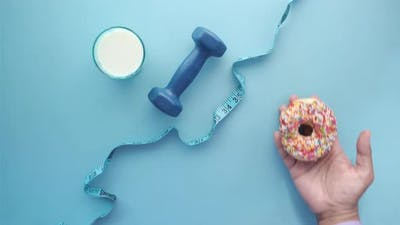 Measuring Tape Wrapped Around a Dumbbell and Donuts on Table
