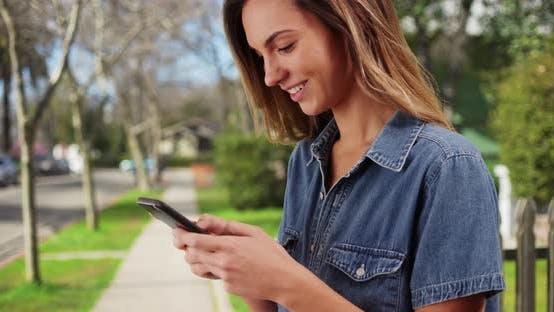 Thumbnail for Nahaufnahme von weißen Millennial Mädchen stehen in der Nachbarschaft, SMS auf Handy