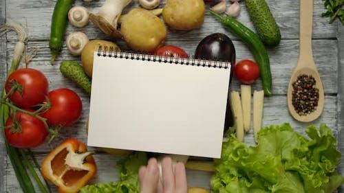 Rezeptbuch auf Tisch geworfen mit vegetarischem Essen.