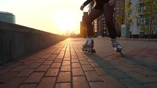 Jambes minces d'une fille patineuse artistique en patins à roulettes Montez sur les pavés.