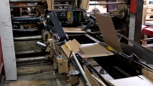 Conveyor line for the production of  boxes. Machine carves cardboard boxes