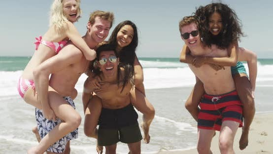 Portrait of young group of friends piggyback on the beach