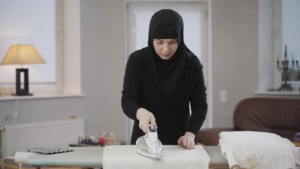 Thumbnail for Portrait of Beautiful Muslim Lady in Traditional Clothes Ironing and Folding Laundry at Home