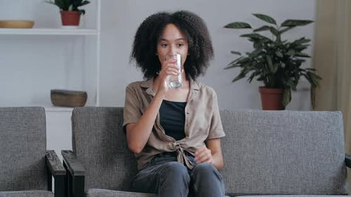 Young African American Woman Sitting on Couch at Home in Stuffy Room Resting Relaxing, Quenching Her