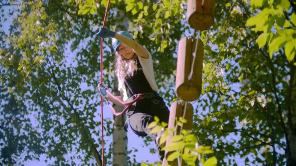 A Woman Walks on Logs Suspended in the Air Between Trees in the Forest - Extreme Rope Adventure