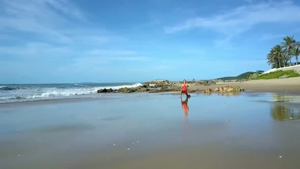 Thumbnail for Girl in Red Stands in Yoga Position on Wet Sand