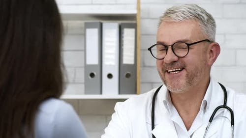 Cheerful Doctor Talking To Female Patient During Medical Appointment Indoor