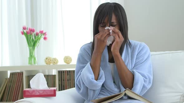 Thumbnail for Sick African American woman blowing nose into tissue