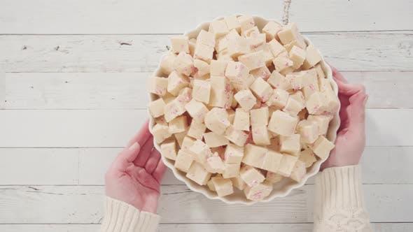 Flach liegend. Schritt für Schritt. Zuckerrohr Fudge in kleine Würfel geschnitten auf einer weißen Servierplatte