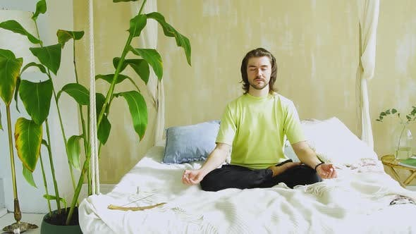 Young Man Sitting in Yoga Pose in Bed and Concentrating