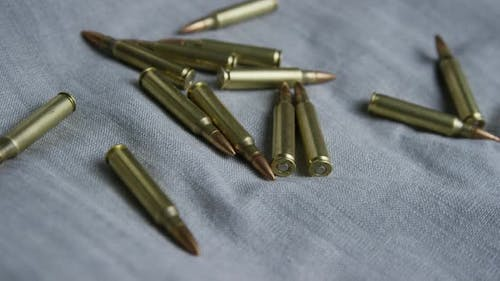 Cinematic rotating shot of bullets on a fabric surface - BULLETS 100