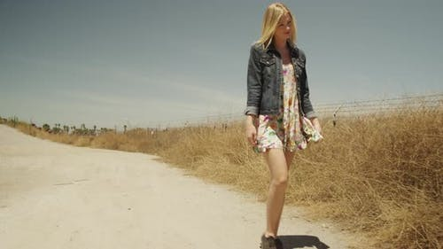 Cute caucasian white girl strolling on isolated road